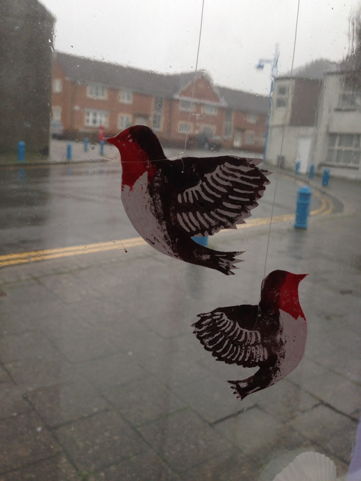Paper robins displayed in a window.